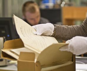 Nærbilde av en persons hender. Vedkommede har hvite hansker og blar i arkivmateriale.