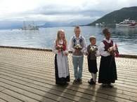 Fire spente elever som skal ta i mot kongeparene når de ankomemr Harstad