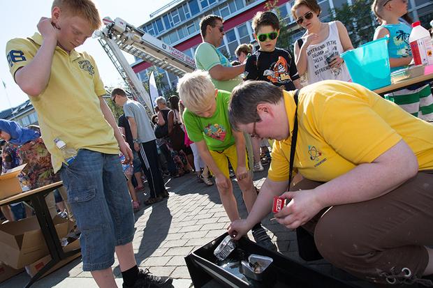 Fh. Vitensenterets Anne Bruvold viser Dennis og Rasmus hvordan man lager brannstyrte båter under Vanndagen 2013.