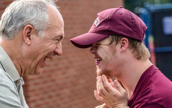 Bilde av en voksen mann og en ung gutt med Down syndrom som ser på hverandre og smiler bredt