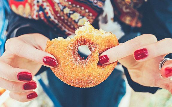 Bilde av hender som holder en halvspist donut med sukker på