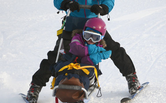 Bilde av et barn i en sitski og en voksen som styrer, bak.