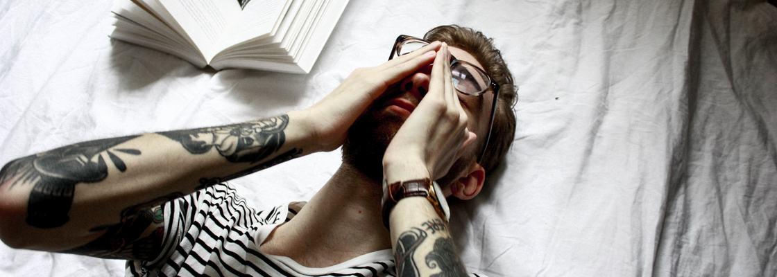 Illustrasjonsbilde av ung mann som holder hendene mot hodet, liggende på en seng