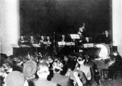 Sorthvittfoto av orkesteret med publikum i forgrunnen