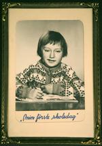 """Innrammet sorthvittportrett av en smilende, kortklipt pike i syvårsalderen. Under bildet står det """"Min første skoledag"""""""