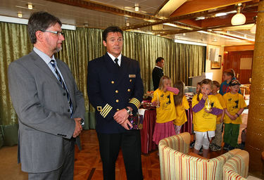 Kaptein Pål Mæland, som er fra Tromsø, fikk gave fra ordfører Arild Hausberg. I bakgrunnen er Haiklubben fra Norrøna barnehage som ga en rose til alle passasjerene. Foto: Ronald Johansen, iTromsø