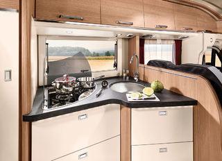ET L-FORMET kjøkken der du får litt mer arbeidsplass ved å bruke deksler både på de elektriske platene og vasken.