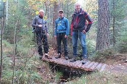 Bjarne Røsjø. Elegant kryssing av en liten bekk, brua er lagd av materialer som kommer fra skogen. Fra venstre: Bjørn Enoksen, Vegard Mæland og Øyvind Rørslett.