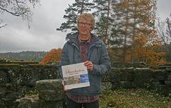 Even Saugstad med den nye boka foran ruinene etter den berømte dragestilvillaen på Sarabråten. Foto: Bjarne Røsjø.