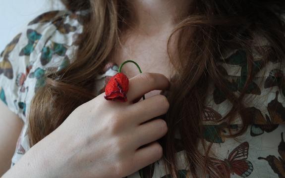 Bilde av en jente som holder en død blomst