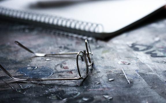 Bilde av briller og kladdebok på et bord