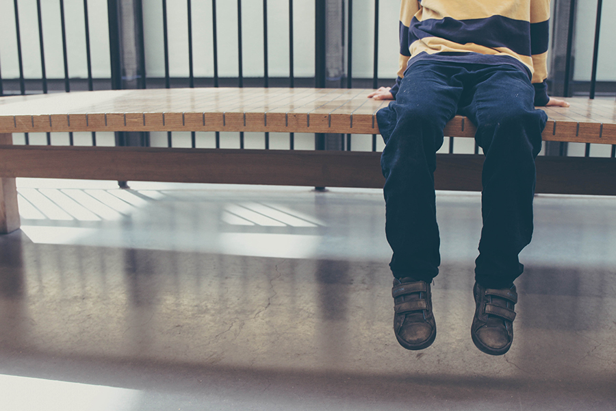 Bilde av et barn på en benk, man ser bare fra knærne og ned.