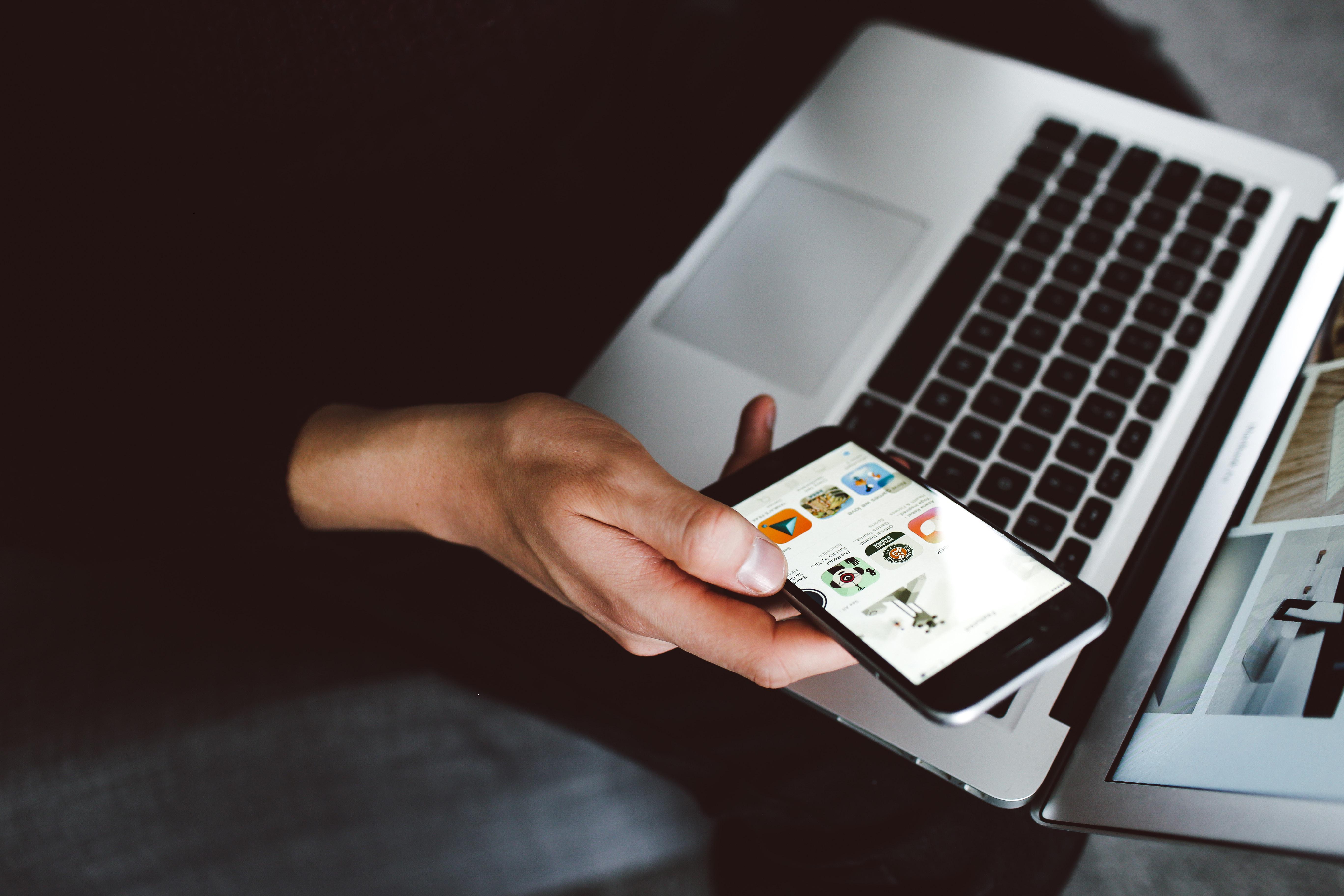 Bilde av en hånd som holder en mobiltelefon over en åpen laptop