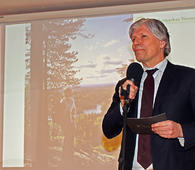 Ola Elvestuen ble den første statsråden som besøkte et årsmøte i Østmarkas Venner. Bildet på veggen bak ham viser Sverre M. Fjelstad på Tonekollen, mens han skuer ut over det området som kan bli en ny nasjonalpark. Foto: Bjarne Røsjø.