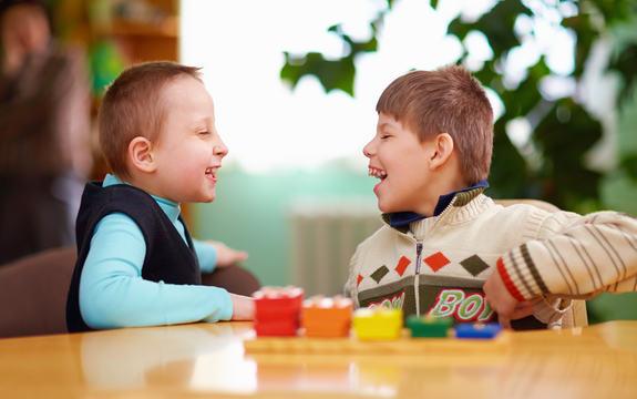 Bilde av to små gutter som ser på hverandre og ler
