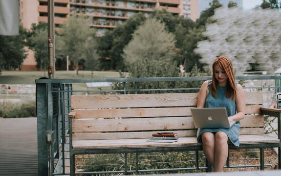 Jente på en benk med datamaskin i fanget.