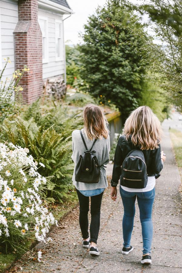 To jenter med ryggen til som går ned langs en vei