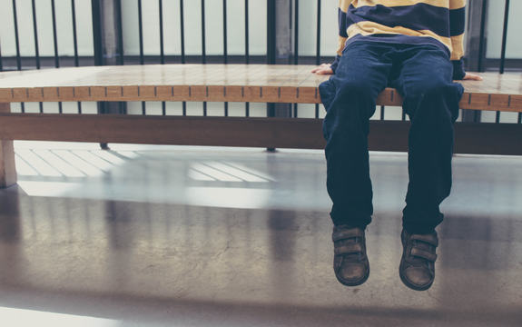 Bilde av en benk der man bare ser beina til et barn