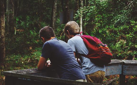 To gutter som lener seg på et rekkverk. Bildet er tatt bakfra.