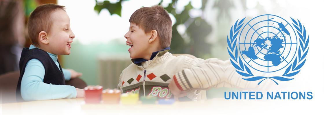 I anledning FN dagen 3. desember, to små gutter som sitter ved et bord og ler hjertelig til hverandre