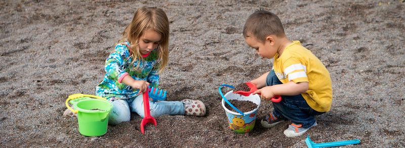 to barn leikar med spade og bøtte i sandkasse