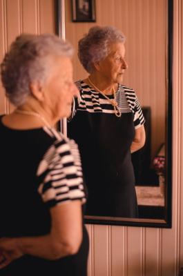 Eldre kvinne foran speil