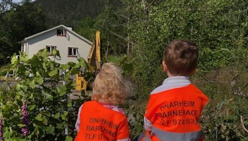 To barn ser på gravemaskin
