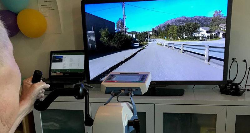 mann syklar ergometersykkel og ser på tv - foto