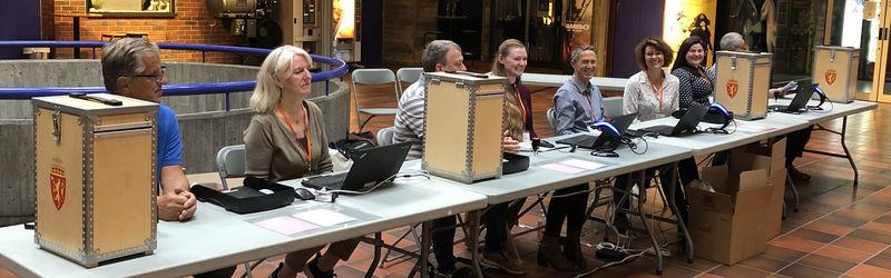valfunksjonærar (folk) sit ved bord og tek i mot røyster i vallokale - foto
