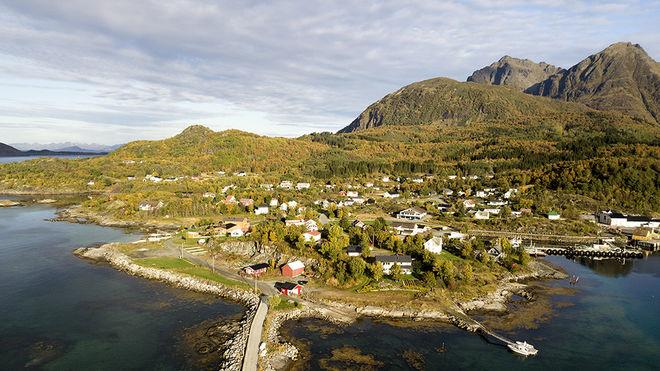 Dronefoto over bygda skutvik: havn, hus og fjell