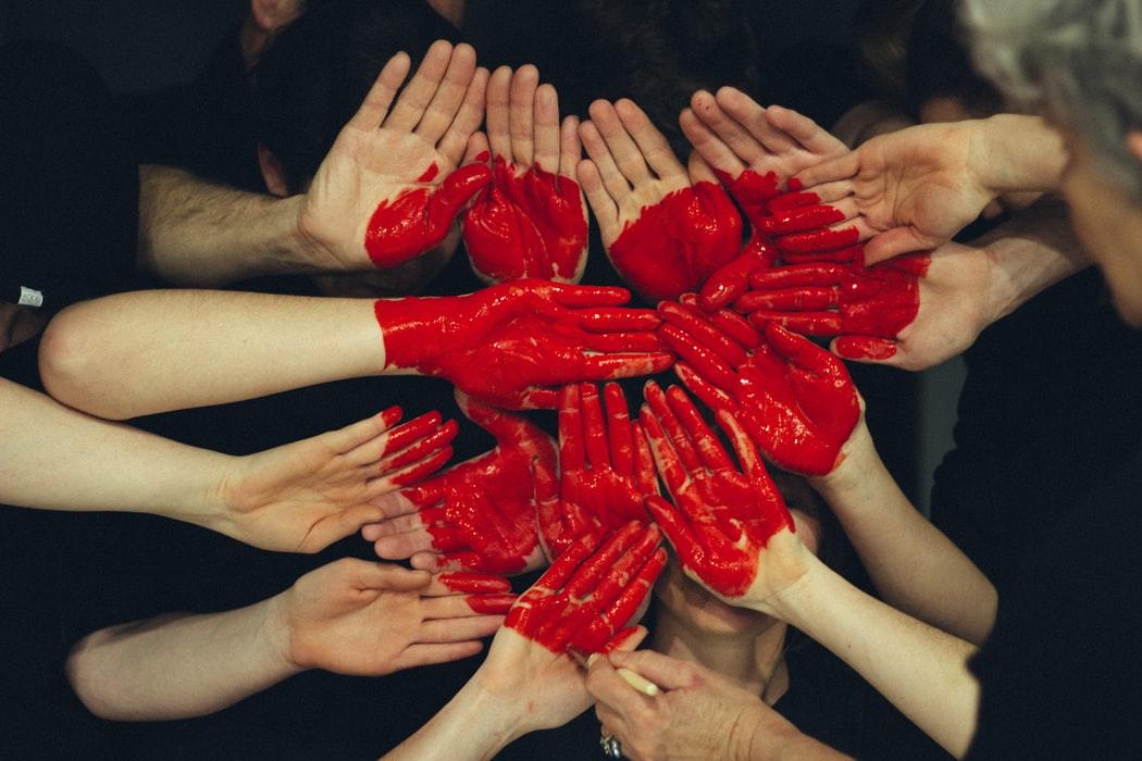 Mange hender som er samlet og har påmalt et rødt hjerte