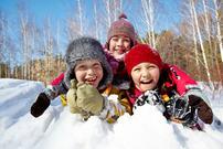 Tre barn som ligger i snøen og smiler mot fotografen.