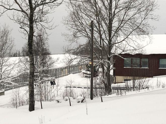 Snø og traktor som brøyter mellom to bygg