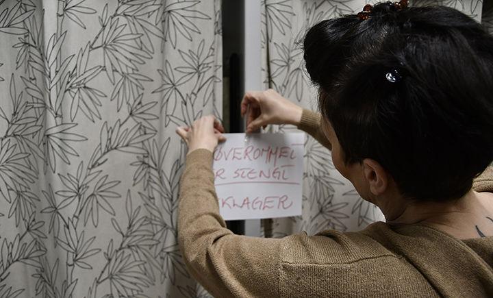 STENGER: Avisen møtte butikkmedarbeider Trine Seppola. Her henger hun opp stengt-skiltet på prøverommene. FOTO: TORBJØRN KOSMO