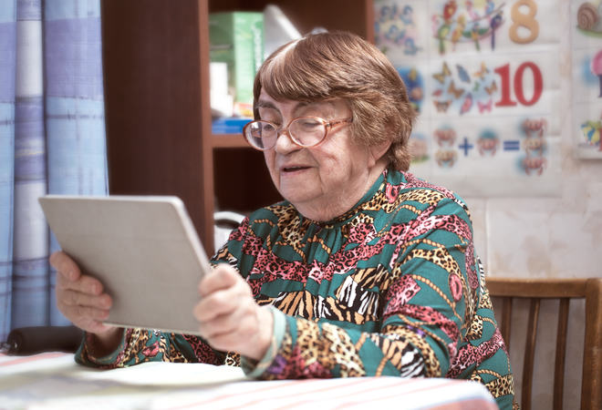 Elderly woman in glasses watching something on pad