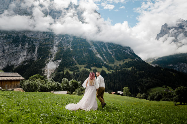 beautiful young bride and groom walking on mountain meadow with clouds in Alps