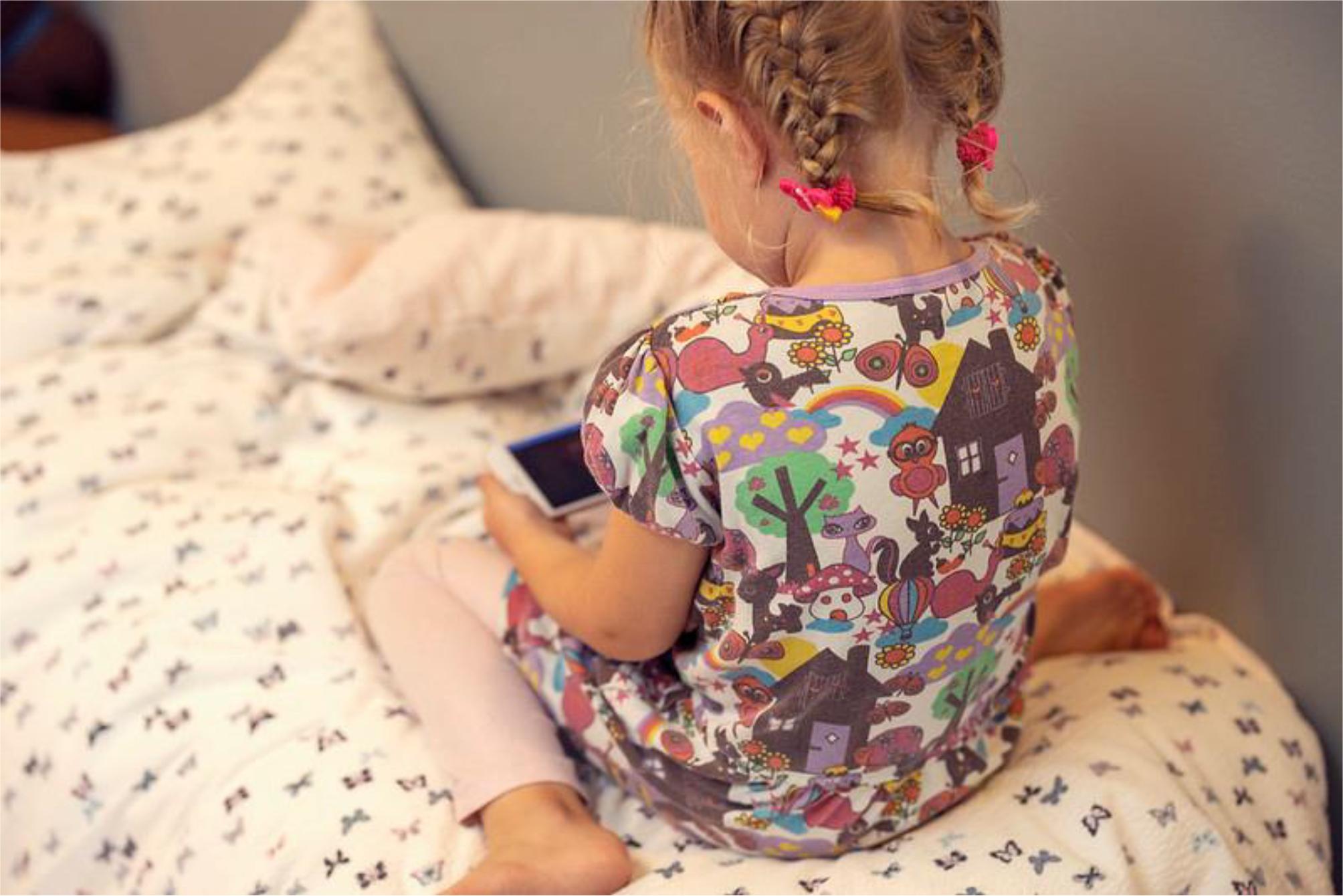 Bildet viser en liten jente med en telefon og bildet er fotografert bakfra