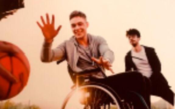 Ung mann som spiller basketball i rullestol