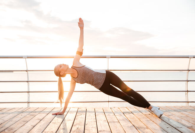 Sporty fitness woman doing planking yoga exercises outdoors