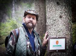 Sverre M. Fjelstad ved det første verneområdet-skiltet som ble hengt opp ved turstien til Dølerud i april 2015. Foto: Per Erik Fjeld.