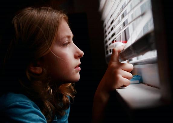 Bilde av ung jente som kikker ut av et vindu gjennom persienner. Foto: Sharon McCutcheon/unsplash