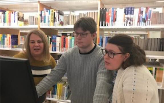 Bilde av tre personer som ser på en dataskjerm
