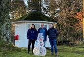 tre personar står ute ved julelys