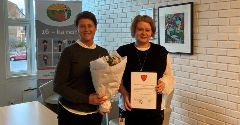 To damer ved sida av einannan med diplom og blomar.