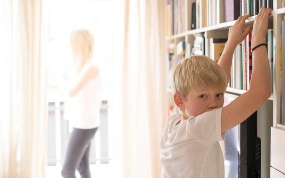 Bilde av en gutt som lener seg mot en bokhylle og ser mot fotografen