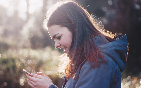 En ung jente holder en mobil i hånda og smiler mot skjermen. Foto