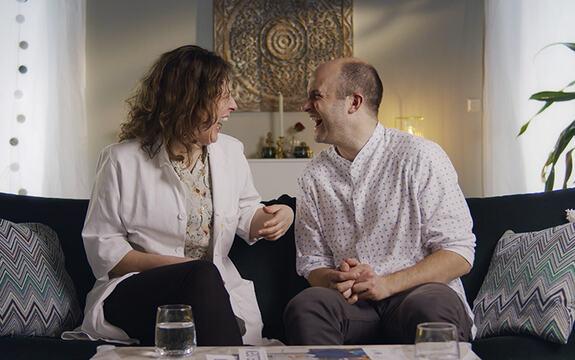 Bilde av to mennesker i en sofa som ler hjertelig mot hverandre.