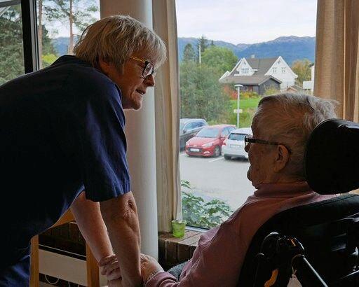 sjukepleiar - dame står ved eldre dame i rullestol. foto