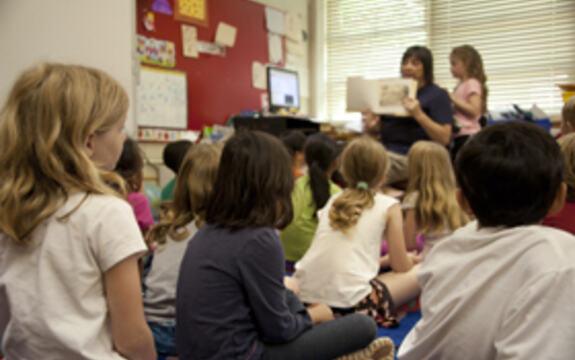 Bilde av barn som sitter på gulvet i et klasserom mens læreren i front holder opp en bok.