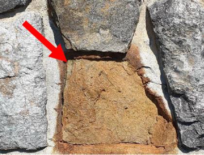 Forvitret syredannende stein i murvegg